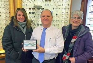 our eye care team, holding chamber of commerce plaque