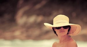 Woman wearing sunglasses and a hat for UV protection