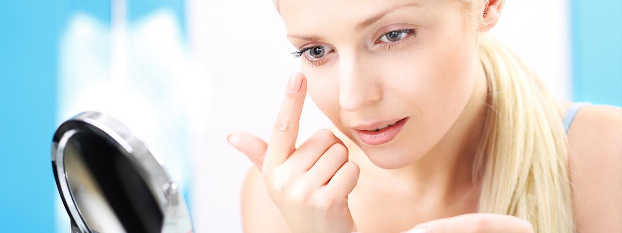 Woman applying contact lens in Lantana, FL