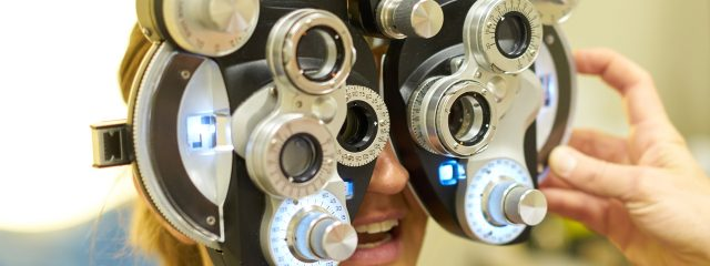 Eye care, woman using a phoropter in Whitehall, PA,