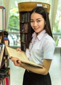 Girl in library holding book, Ortho-K, Optometrist, Milton, ON