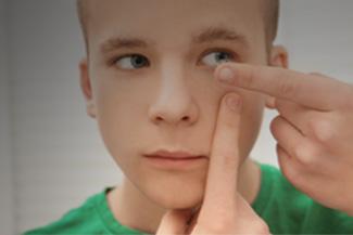 Optometrist, boy putting on a contact lens in Scranton, Pennsylvania