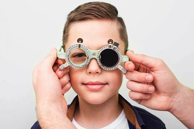 Optometrist Putting On The Boy Special Glasses To Restore Visual