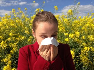 Girl surrounded by flowers sneezing, allergies - optometrist, Round Rock, TX