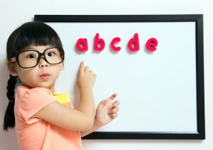 girl with glasses reading alphabet