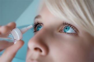 Optometrist, woman applying eyedroppers for dry eye in Freelton, ON