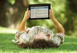 man reading news on laptop