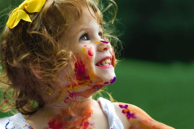 Little girl covered with paint