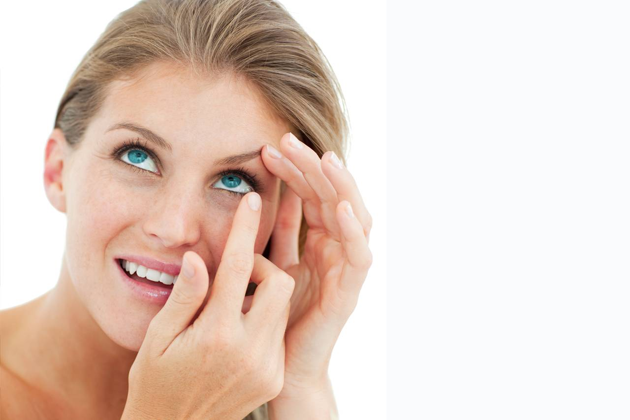 attractive blond putting in contact lens in Clay, New York