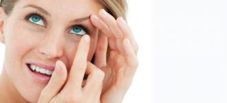 blonde woman putting in contact lenses