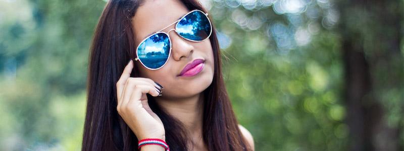 brunette wearing tinted blue designer eyeglasses