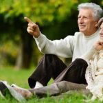 old couple sitting in field