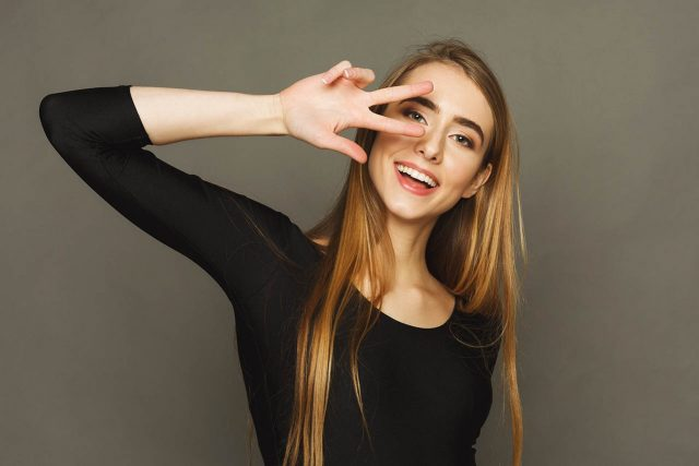 Pretty Cheerful Woman Gesturing With Two Fingers Near Eyes. Youn