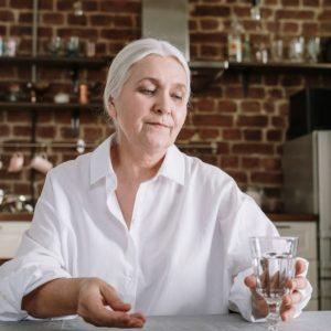 senior woman taking her medicine 640