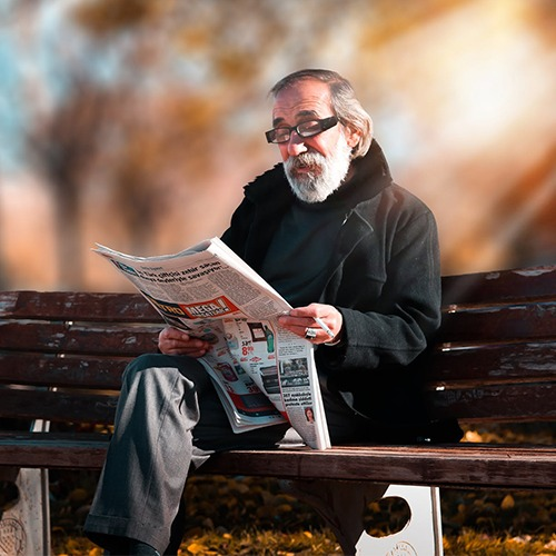 Old man sitting on bench reading newspaper