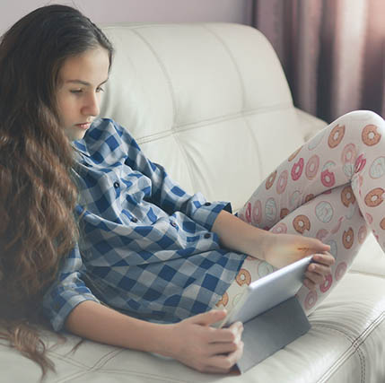 Girl with tablet, sitting on couch