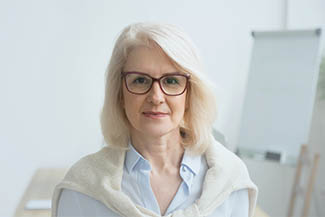 Confident Aged Businesswoman Wearing Glasses Looking At Camera,