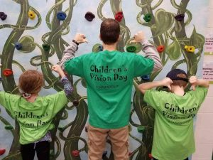 Clio optometrist N. Belill OD and children at the Children's Vision Day event, Flint Children's Museum