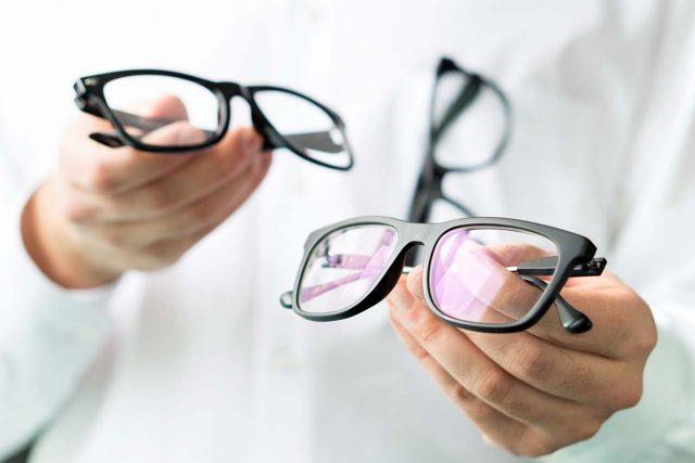 Eye doctor holding pairs of eyeglasses