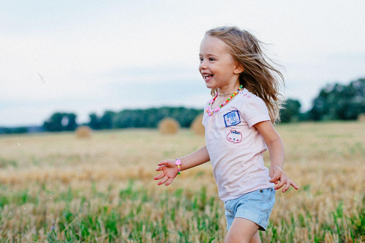 little girl running in the field
