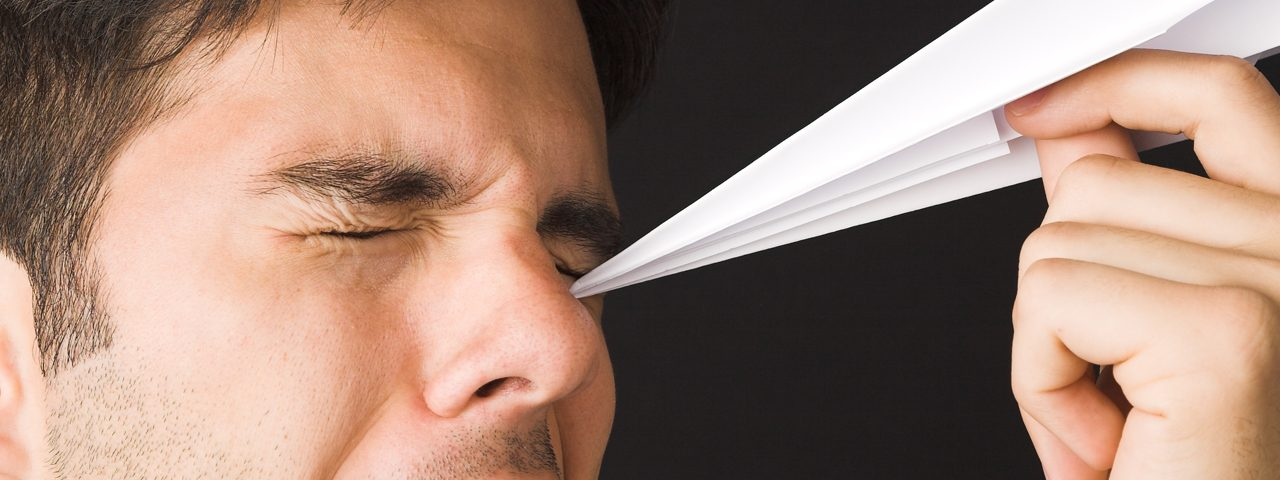 Man Poking Eye with Paper Airplane 1280x480 e1542638611185