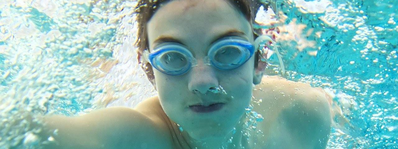 Eye care, teenager swimming wearing specialty eyewear in Katy, TX