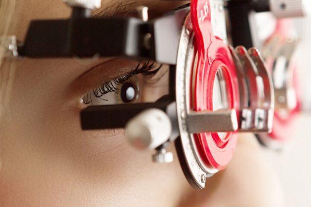 Girl covering her eye in front of eye chart, for eye exam