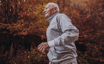 Senior Runner In Nature. Elderly Sporty Man Running In Forest Du