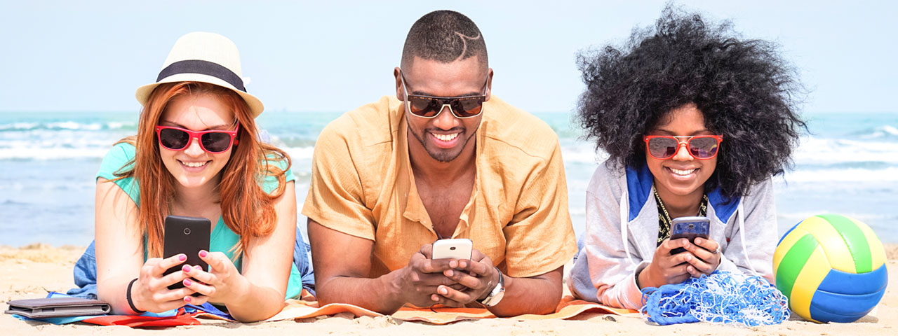 Man and Women wearing sunglasses, playing on phones