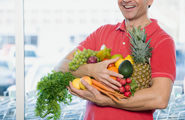 Man holding fresh fruit and vegetables at grocery store