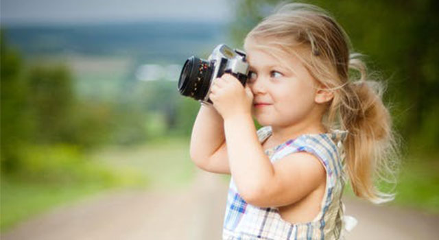 child taking photograph