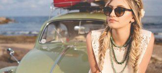 Woman wearing sunglasses, sitting on car in Laguna Beach