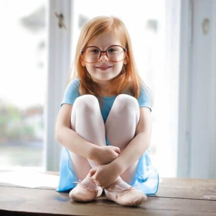 child girl redhead smiling glasses blue ballet dress