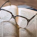 Pair of eyeglasses on a book