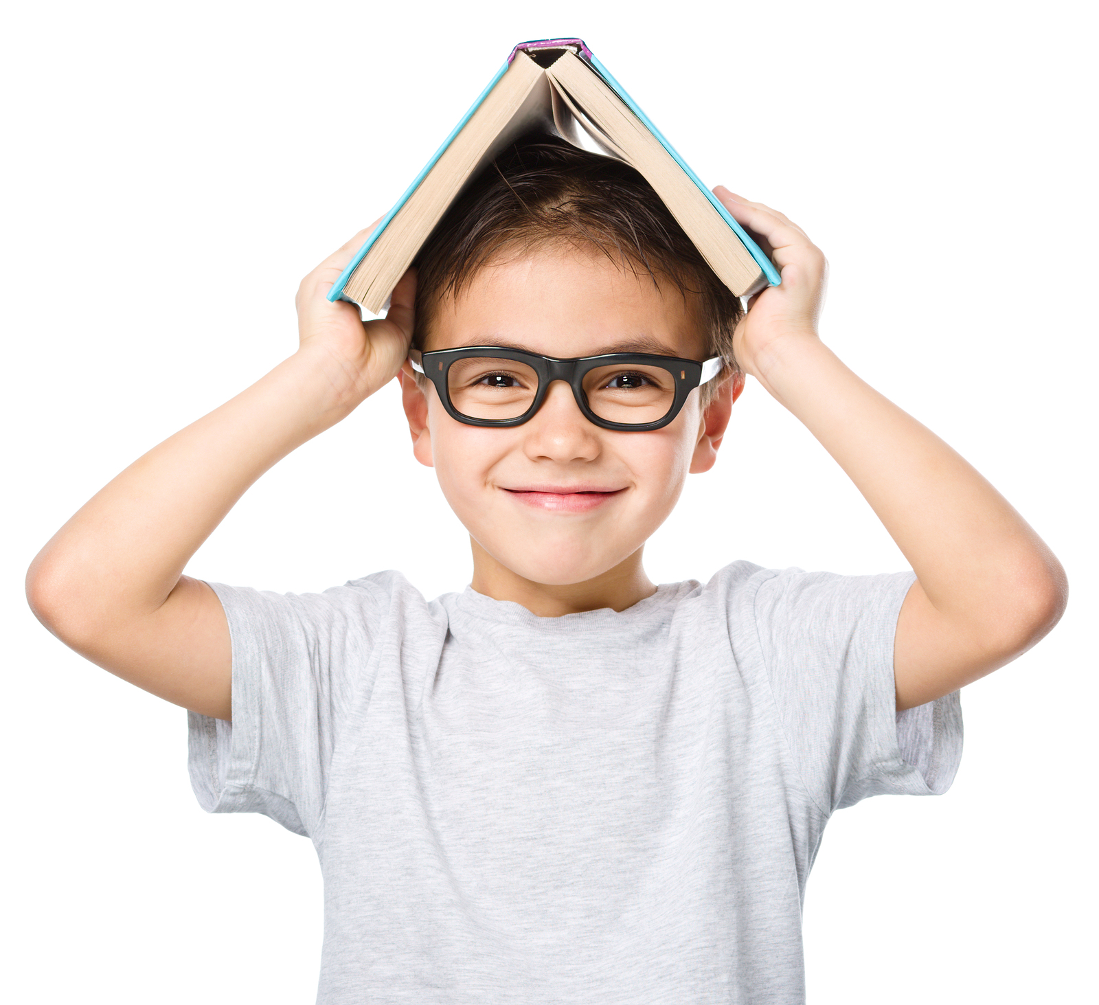 Cute little child plays with book while wearing glasses, isolate