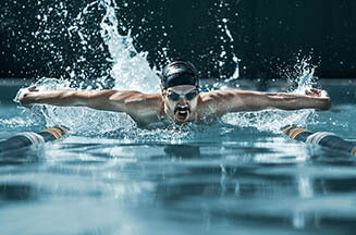 The Dynamic And Fit Swimmer In Cap Breathing Performing The Butt