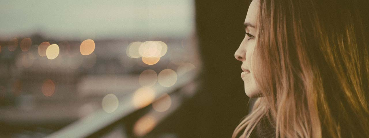 WOman looking out window, suffering from dry eyes