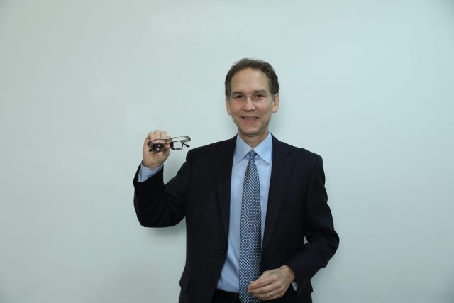 Dr. Pino holding a pair of low vision glasses