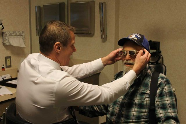 Dr. Jacobi helping patient trying on a new pair of low vision glasses