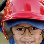 Cute little boy wearing glasses, playing baseball