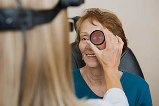 Female optician examining senior womans eye with binocular indi