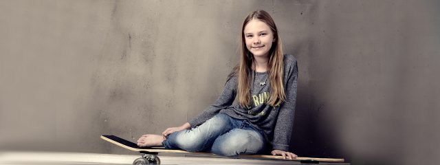 Eye doctor, teenage girl sitting on a skateboard in Plano, TX