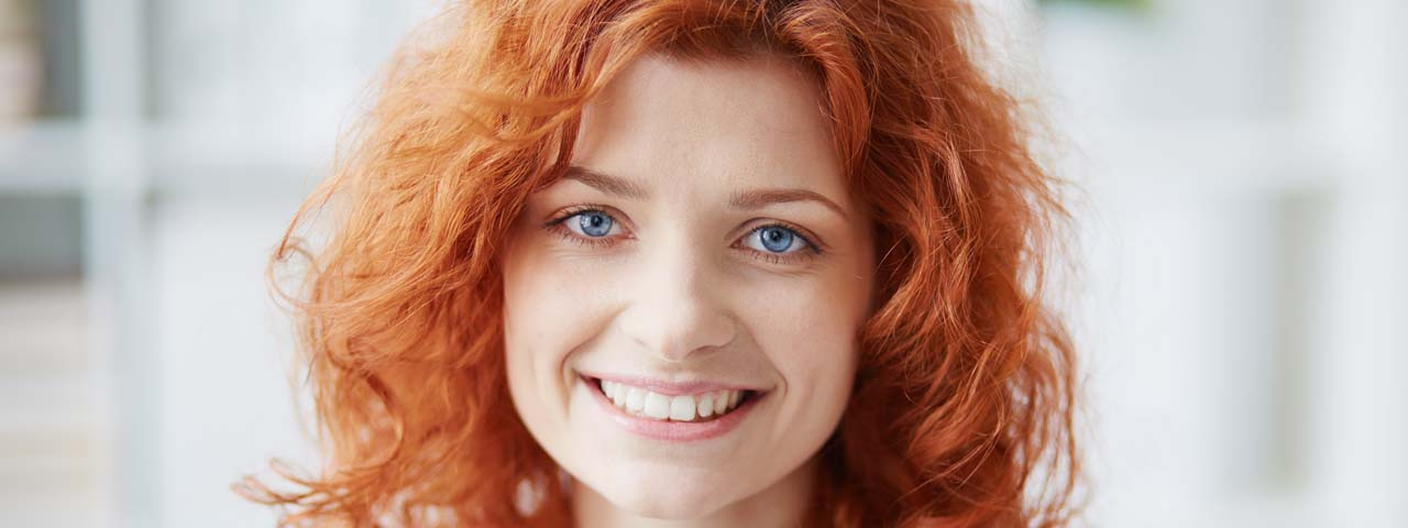 optometrist, redheaded woman with dry eye, smiling after treatment