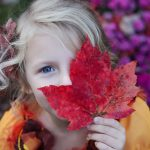 optometrist, child covering one eye with leaf in Long Grove, Illinois
