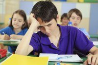 boy in purple shirt frustrated in the classroom