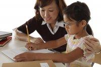young girl doing homework with mom