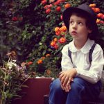 Boy wearing Hat Sitting in Garden