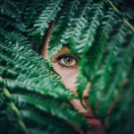 woman showing single green eye through leaves