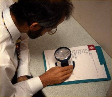 Man using magnifier to help with Low Vision
