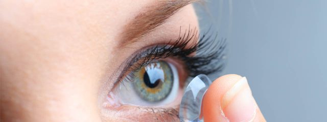 Eye doctor, woman putting on disposable contact lens in Oconomowoc, Watertown and Pewaukee, WI